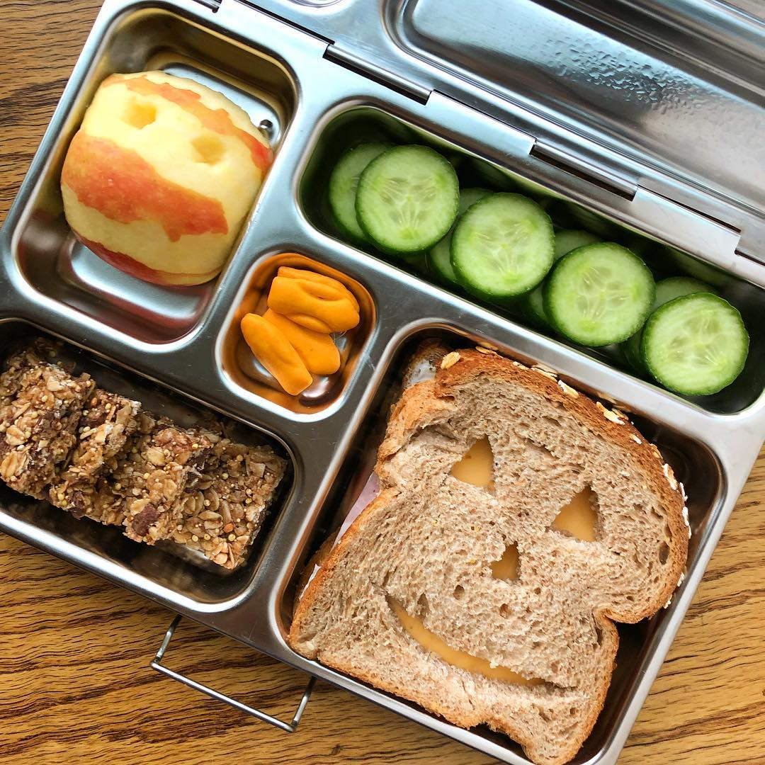 "If you only have 10min to prepare the lunchbox and you still want to make a ""theme"" here you are an idea: ham&cheese sandwich (one knife, three triangles, one semicircle) + apple zombie (roughly slice the peel three times and make two holes for the eyes) + cucumbers + crackers + gluten free dark chocolate seeds bar @kindsnacks  Happy Thursday"
