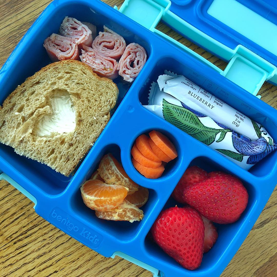 "Easy kiddo lunchbox for Valentine (lol, this year I'm all for easy and simple decorations, done in 30sec). I simply used an heart shaped cookie cutter to cut out the top of the sandwich.  Multigrain cream cheese sandwich with rolled rosemary ham (little one is still in the ""deconstructed"" sandwich phase 🤷‍♀️) + strawberries + tangerine + carrot + low sugar yogurt @siggisdairy Lately I've been in the deep research of stick yogurts for the kids not super loaded with sugars…to be sincere. It's difficult!! 🤦🏼‍♀️🤦🏼‍♀️ I really do not understand why supposedly kid friendly products are in fact the worse for kids. 😡😖 That being said I selected few stick yogurts that have the minimum added sugar amount on the market"
