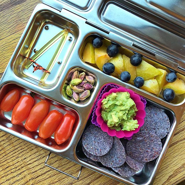 "Guacamole & chia multigrain chips today 😉 Plums + grapes + tomatoes + pistachios + honey stick.  My guacamole is on the basic side 😁: local Hass ripen avocado + pinch of salt + squeeze of lemon. That's it, and that's how my kids like it 😉 Adding guacamole to the lunchbox can be tricky: oxidation of color and food contamination are the challenges. Those are my tricks: – for the contamination I use a taller silicone container that doesn't leave any space between the top and bottom part of the lunchbox. So when I close it the container attaches to the top and even if my kids shake the lunchbox the guacamole doesn't touch the chips. Soggy chips are not appealing, I know 😬 I also tried the small containers with lid to insert in the lunchbox but my kids complain that it's difficult to open them 🤔 – oxidation. No matter what you do, the bright green color of the avocado will fade into a brownish one as soon as you open it. Still, you can slow down the process adding lemon to the guacamole (already required by the recipe 😉) and squeezing few more drops on top once you place the guacamole in the containers.  Also, as it's a matter of time, I prepare the guacamole in the morning before school and not the night before. I add everything else the night before and only the guacamole in the morning.  Do you have any more ""guacamole"" tips to share? Ciaoooo"