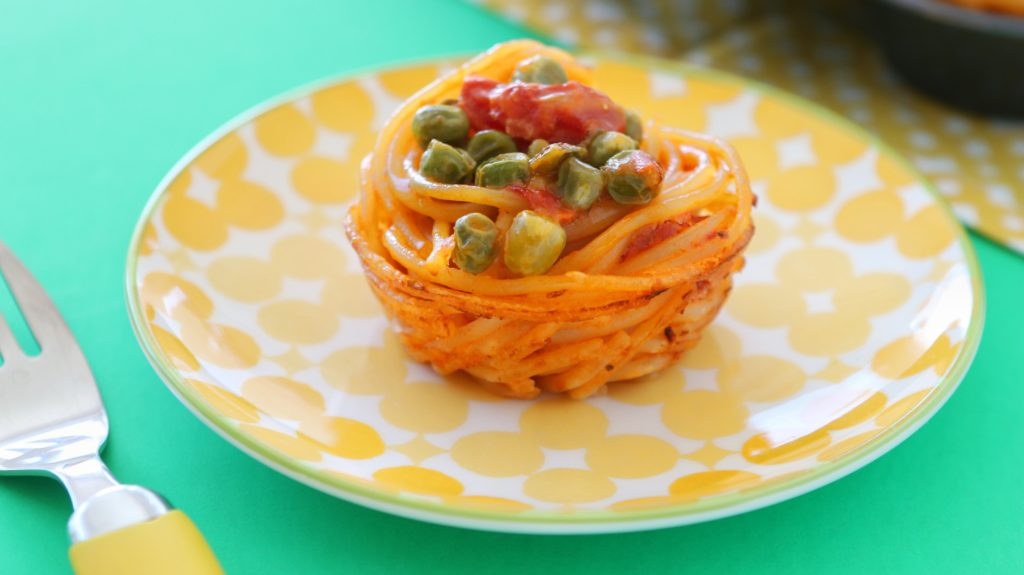 Spaghetti Muffins on a yellow plate with a yellow fork.
